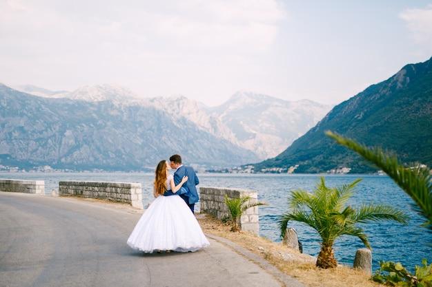 De bruid en bruidegom lopen langs de weg bij perast en kussen, achteraanzicht