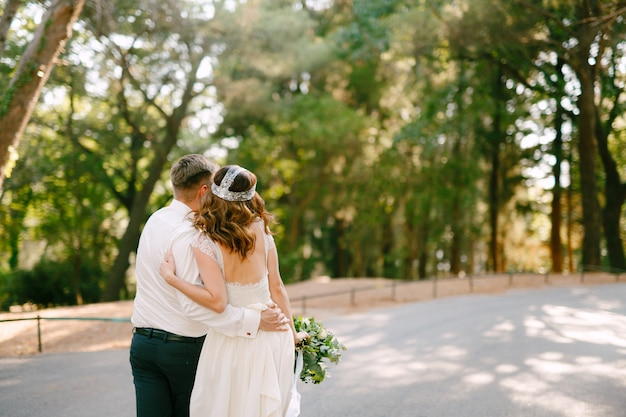 De bruid en bruidegom lopen langs de weg in het park en knuffelen elkaar, de bruid houdt vast