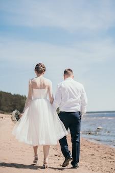 De bruid en bruidegom lopen over straat bij de handen, een stijlvol jong stel loopt man en vrouw...