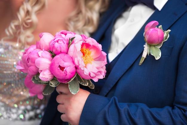 De bruid en bruidegom met een boeket pioenrozen