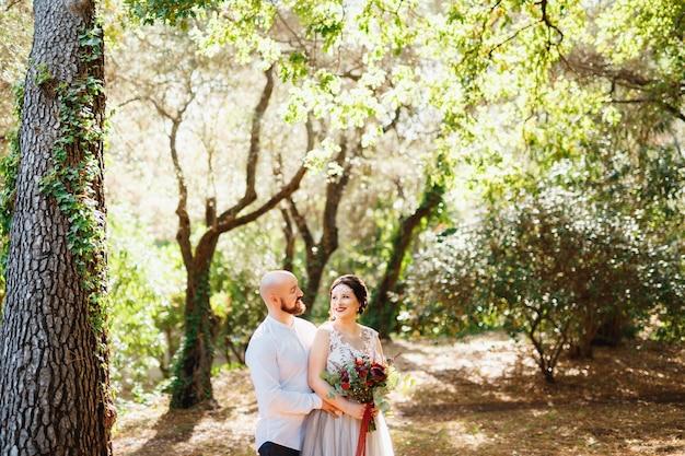 De bruid en bruidegom met een boeket staan knuffelen tussen de bomen in een olijfgaard