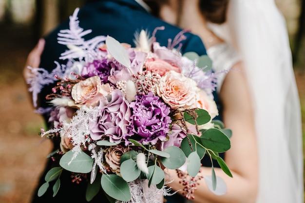 De bruid en bruidegom met een bruiloft boeket, hand in hand en staande op de huwelijksceremonie van de buitenlucht in de achtertuin van de natuur.