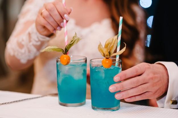 De bruid en bruidegom met een kleurrijke cocktail in haar hand