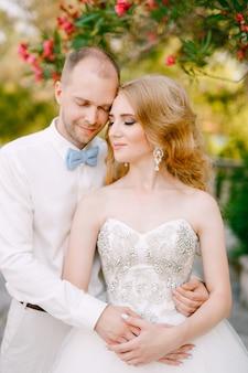 De bruid en bruidegom nestelen zich teder tegen een bloeiende oleanderstruik bij de