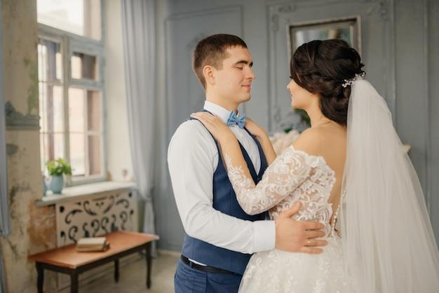 De bruid en bruidegom omhelzen elkaar bij het raam. liefde, bruiloft concept. mooie bruiloft, man en vrouw, geliefden man vrouw, bruid en bruidegom.