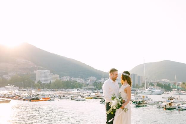 De bruid en bruidegom omhelzen elkaar en kijken elkaar aan tegen de achtergrond van de bootpier in budva