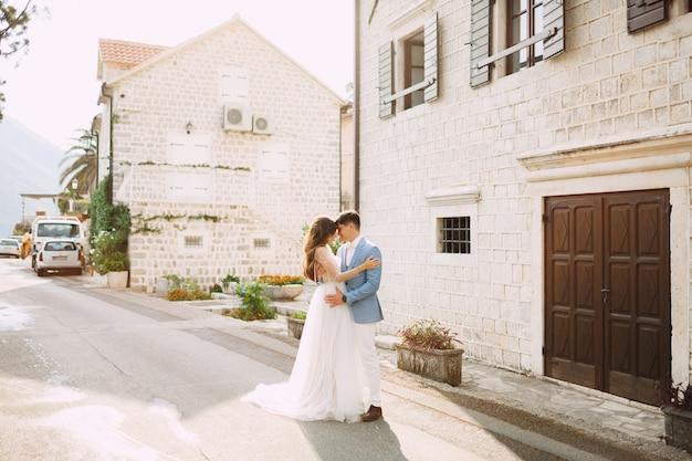 De bruid en bruidegom omhelzen elkaar in de buurt van de prachtige witte huizen in het oude centrum van perast