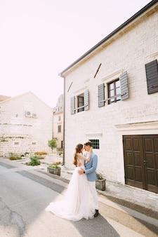 De bruid en bruidegom omhelzen elkaar in de buurt van het prachtige witte huis in het oude centrum van perast