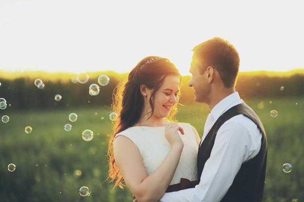 De bruid en bruidegom omhelzen elkaar in het park bij zonsondergang wedding. gelukkig concept.
