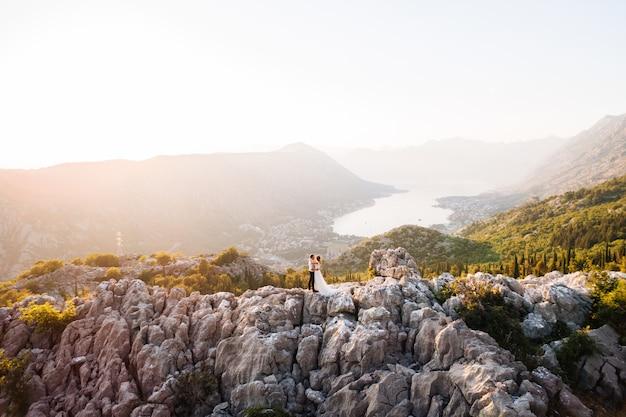 De bruid en bruidegom omhelzen elkaar op de berg lovcen, een schilderachtig panoramisch uitzicht over de baai van kotor