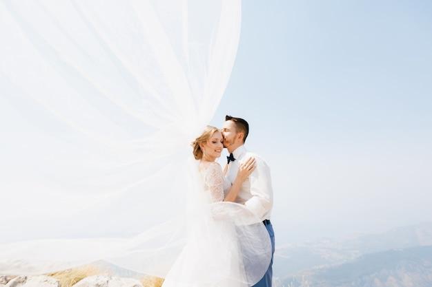 De bruid en bruidegom omhelzen elkaar op de berg