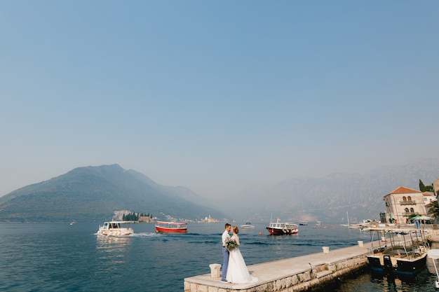 De bruid en bruidegom omhelzen elkaar op de pier bij het oude centrum van perast