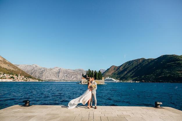 De bruid en bruidegom omhelzen elkaar op de pier in de baai van kotor, achter hen ligt het bergeiland