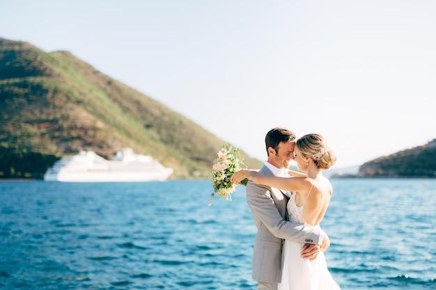 De bruid en bruidegom omhelzen elkaar op de pier in de baai van kotor