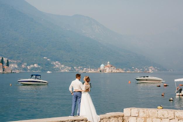 De bruid en bruidegom omhelzen elkaar op de pier in de buurt van het oude centrum van perast boten die in de buurt drijven