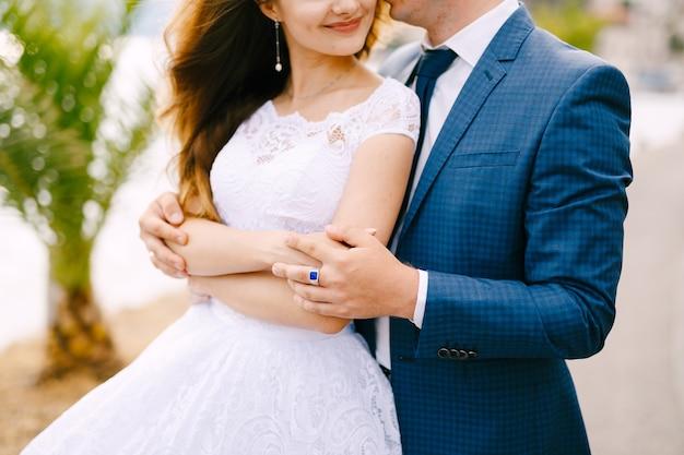 De bruid en bruidegom omhelzen elkaar op de pier in perast, close-up