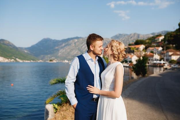 De bruid en bruidegom omhelzen elkaar op de pier in perast, de bruidegom houdt zijn hand in zijn zak