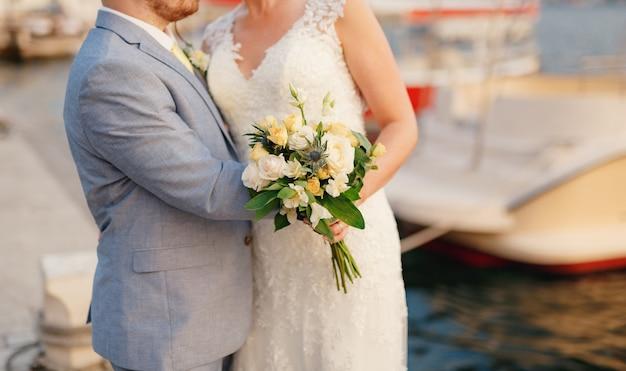 De bruid en bruidegom omhelzen elkaar op de pier