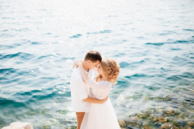 De bruid en bruidegom omhelzen elkaar op de rotsachtige kust en staan op het punt te kussen