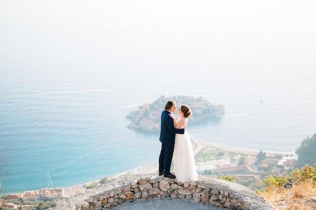 De bruid en bruidegom omhelzen elkaar op het observatiedek met uitzicht op het eiland sveti stefan