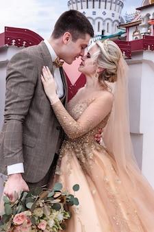 De bruid en bruidegom omhelzen elkaar op straat in het oude kremlin. gelukkig romantisch jong koppel dat hun huwelijk viert.