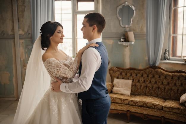 De bruid en bruidegom omhelzen elkaar staan voor het raam. liefde, bruiloft concept. mooie bruiloft, man en vrouw, geliefden man vrouw, bruid en bruidegom.