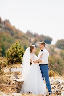De bruid en bruidegom omhelzen elkaar teder bij een houten bankje in de bergen