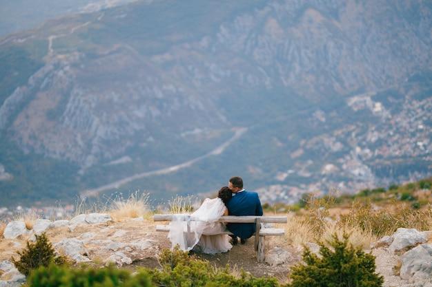 De bruid en bruidegom omhelzen elkaar teder en zitten op een houten bankje in de bergen