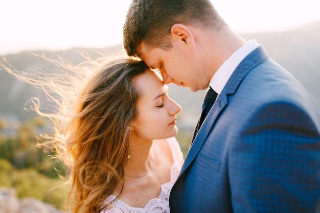 De bruid en bruidegom omhelzen elkaar teder op de berg lovcen, de bruidegom leunde met zijn neus tegen het voorhoofd van de bruid. hoge kwaliteit foto