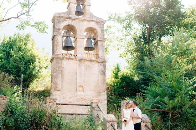 De bruid en bruidegom omhelzen en kussen bij de oude klokkentoren bij de kerk in prcanj