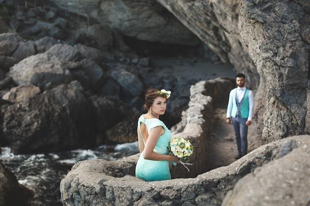 De bruid en bruidegom op de natuur in de bergen aan het water. pak en jurk kleur tiffany. kus en knuffel.