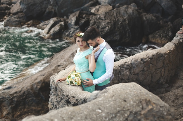 De bruid en bruidegom op de natuur in de bergen in de buurt van het water. pak en jurk kleur tiffany. kus en knuffel.