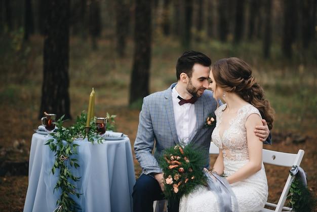 De bruid en bruidegom poseren in het bos