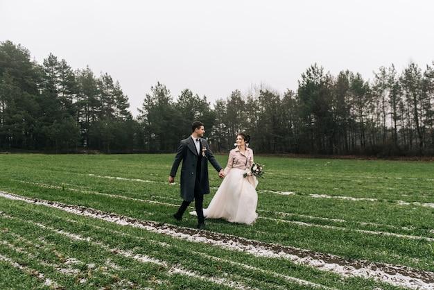 De bruid en bruidegom rennen over het veld met de eerste sneeuw