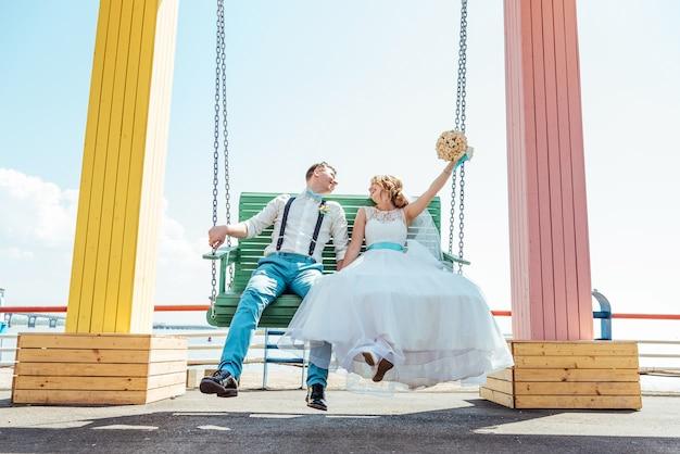 De bruid en bruidegom rijden op een schommel