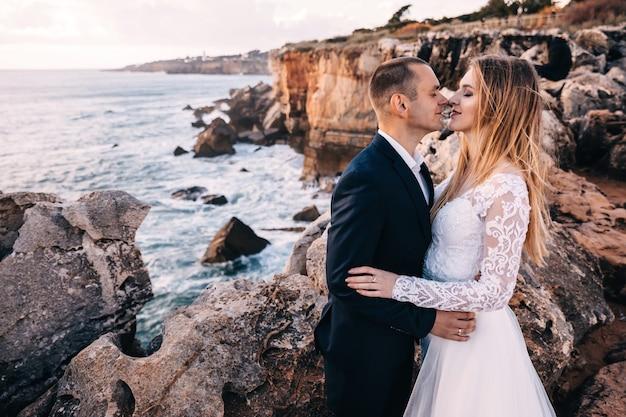 De bruid en bruidegom sloten hun ogen en omhelsden elkaar op de achtergrond van hoge rotsen en zee