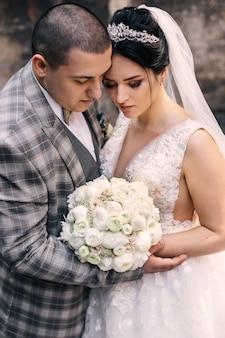 De bruid en bruidegom sloten hun ogen in elkaars armen. bruid met een chique bruidsboeket.