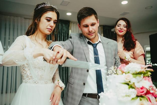 De bruid en bruidegom snijden de taart aan