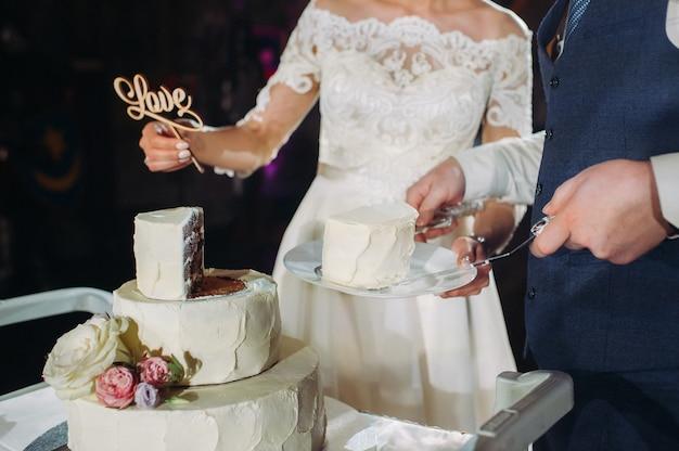 De bruid en bruidegom snijden hun bruidstaart aan. mooie cake met een gesneden en zichtbare vulling. bruidstaart met het woord liefde, het concept van de bruiloft.