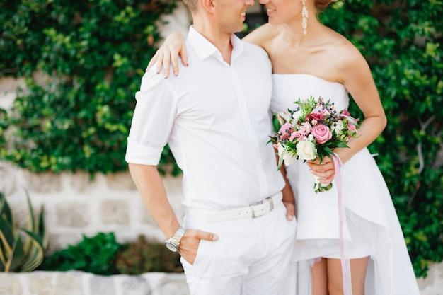 De bruid en bruidegom staan elkaar omhelzend in een prachtig met klimop bedekt wit huis in het oude centrum van perast
