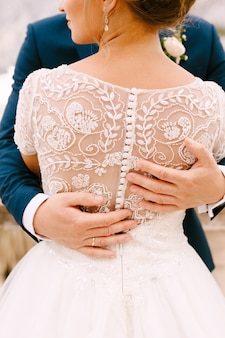 De bruid en bruidegom staan en knuffelen