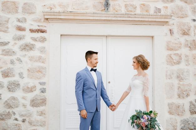 De bruid en bruidegom staan hand in hand bij een witte deur van een prachtig bakstenen huis in de oude stad