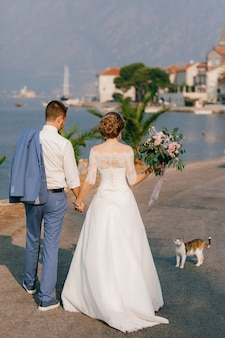 De bruid en bruidegom staan hand in hand op de pier en kijken naar de