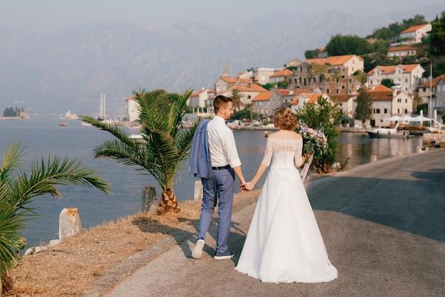 De bruid en bruidegom staan hand in hand op de pier in de buurt van de oude stad