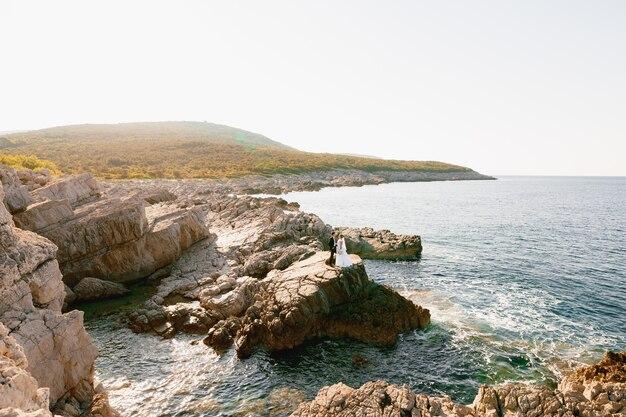 De bruid en bruidegom staan hand in hand op de rotsen bij de zee en kijken elkaar aan