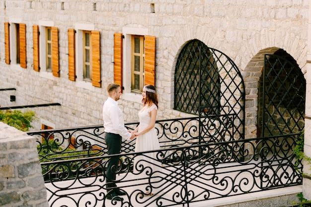 De bruid en bruidegom staan hand in hand op een prachtige gesmede brug in het oude centrum van budva