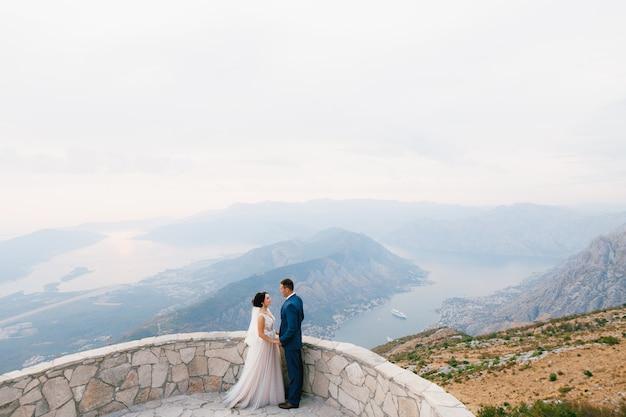 De bruid en bruidegom staan hand in hand op het observatiedek op de berg lovcen met uitzicht op de baai
