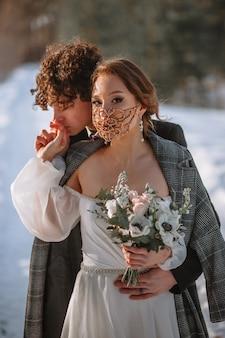 De bruid en bruidegom staan in een besneeuwd bos. de bruid met een fantastisch beschermend masker
