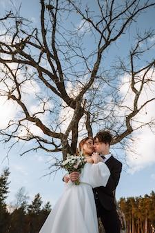 De bruid en bruidegom staan in een besneeuwd bos naast een droge boom