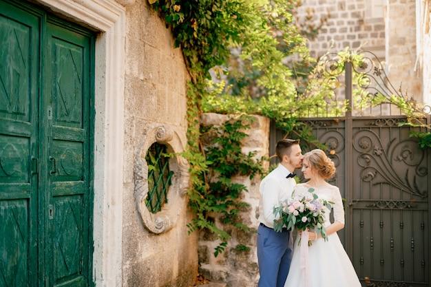 De bruid en bruidegom staan knuffelen in de buurt van mooie oude groene deur de bruidegom kust de bruid op de